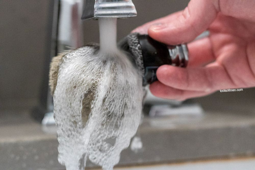 soaking a shaving brush before lathering
